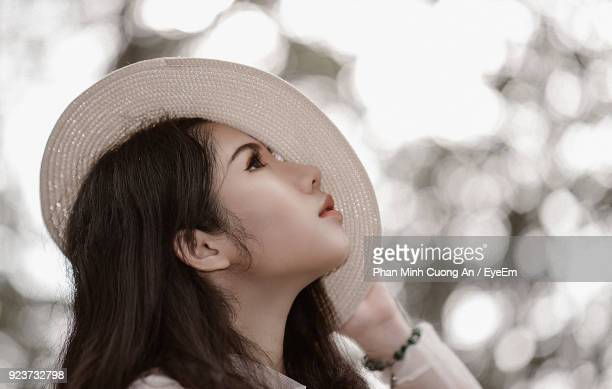 Close-Up Of Young Woman In Sun Hat Against Trees