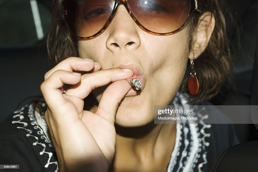 Close-up of young woman in sunglasses smoking a marijuana joint : Stock Photo