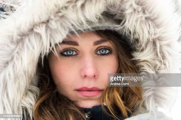 close-up of young woman in winter - brune aux yeux bleus photos et images de collection