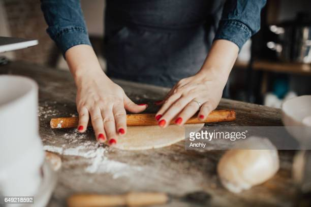 Close-up of young woman kneading dough with rolling pin