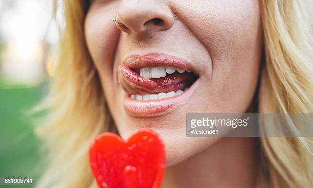 Close-up of young woman licking heart-shaped lollipop