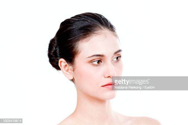 Close-Up Of Young Woman Looking Away Against White Background