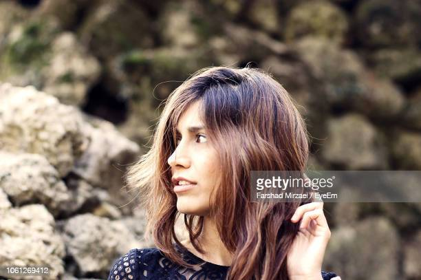 close-up of young woman looking away outdoors - highlights hair stock pictures, royalty-free photos & images