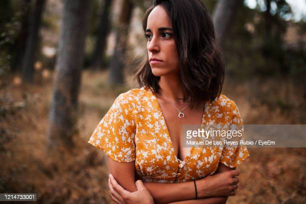 close-up of young woman looking away standing in forest - dress cleavage stock pictures, royalty-free photos & images