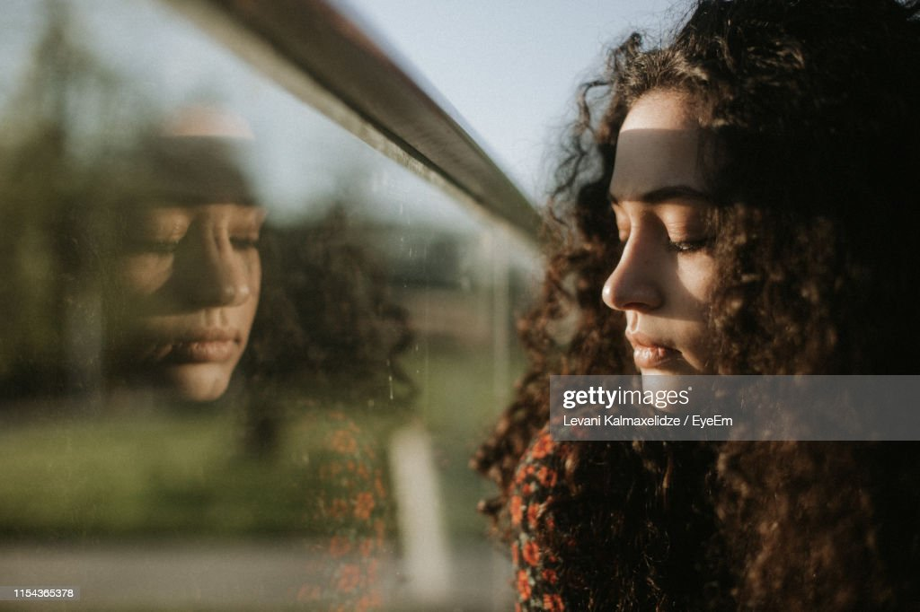 Close-Up Of Young Woman Looking Through Window : Stock Photo