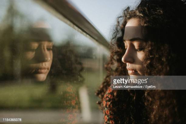 close-up of young woman looking through window - sadness stock pictures, royalty-free photos & images
