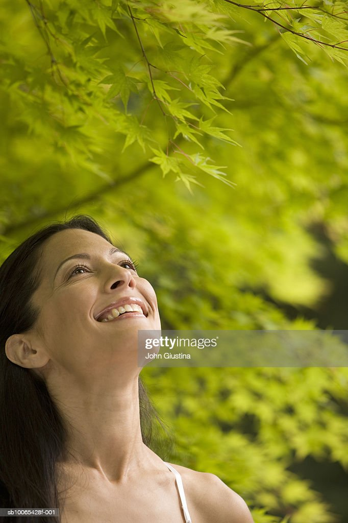 Close-up of young woman looking up, smiling : Foto stock