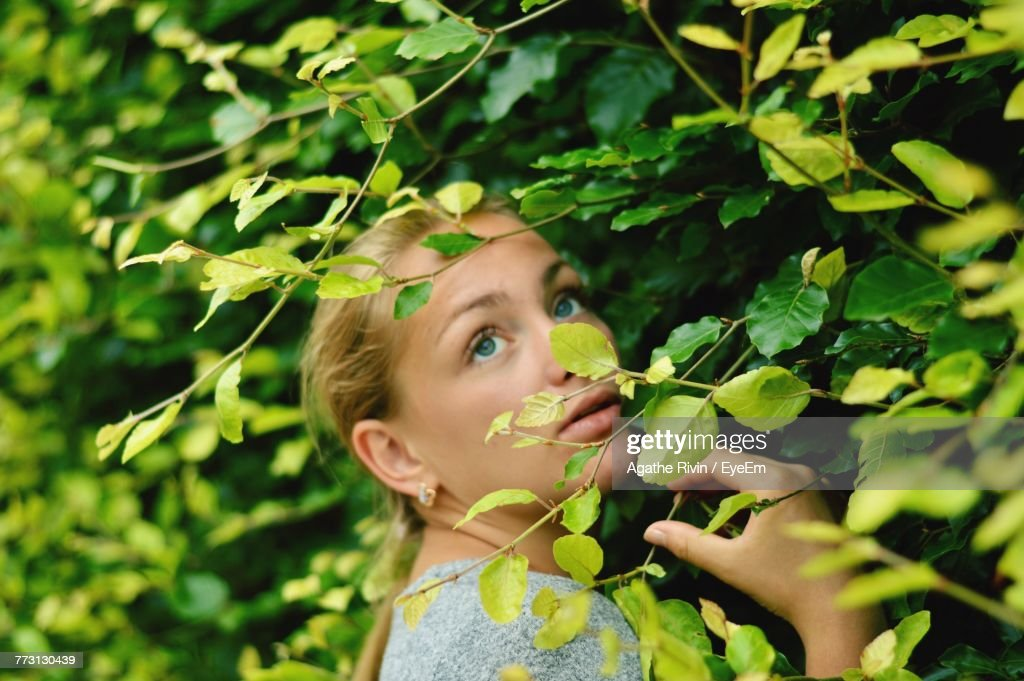 Close-Up Of Young Woman Looking Up While Standing By Plants At Park : Photo