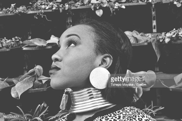 Close-Up Of Young Woman Looking Up While Wearing Earring And Necklace