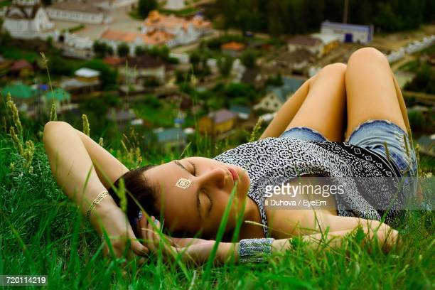 Close-Up Of Young Woman Lying Down With Eyes Closed On Grassy Hill