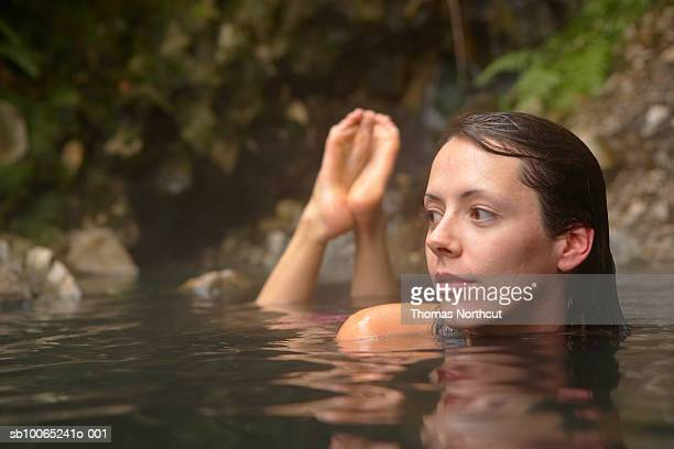 Close-up of young woman lying in hot spring waters
