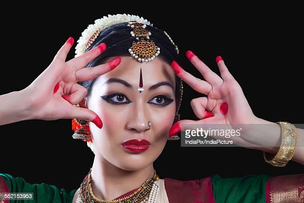 Close-up of young woman making Bharatanatyam gesture called Shakatam on black background