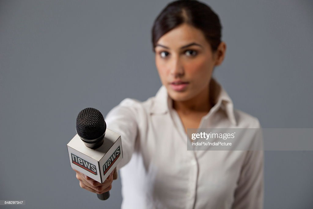 News Detail: Closeup Of Young Woman News Reporter Holding Out