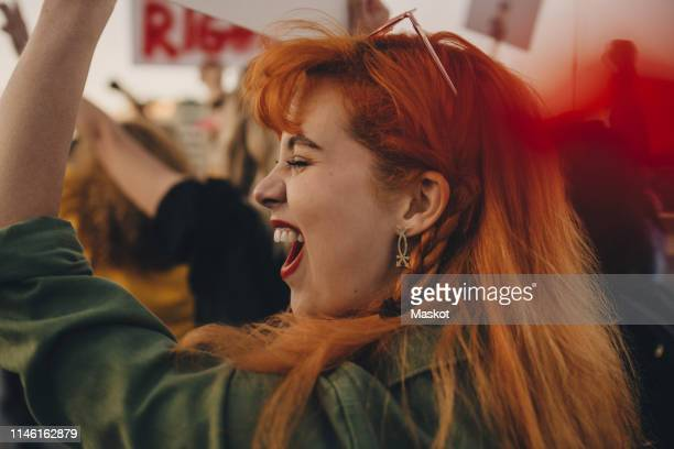 close-up of young woman shouting while protesting for rights - marsch stock-fotos und bilder