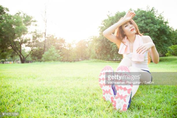Close-Up Of Young Woman Sitting On Grass Field Against Sky