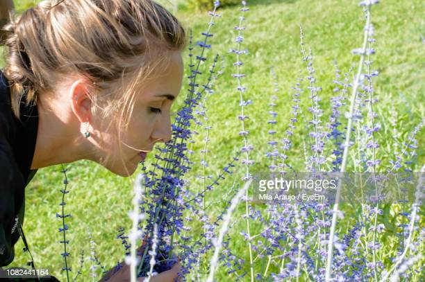 Close-Up Of Young Woman Smelling Flowers Blooming On Field