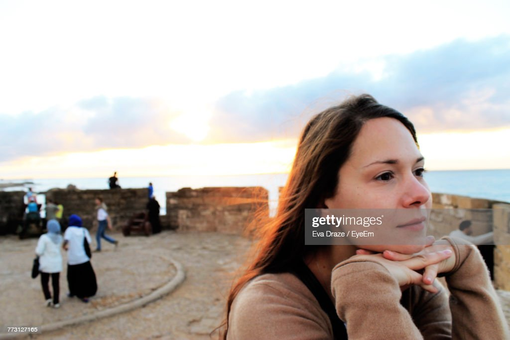 Close-Up Of Young Woman Standing At Beach Against Sky During Sunset : Photo