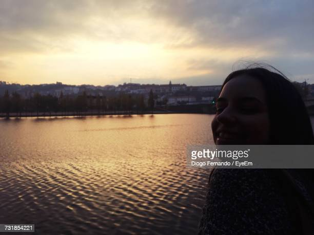 Close-Up Of Young Woman Standing By River Against Cloudy Sky During Sunset
