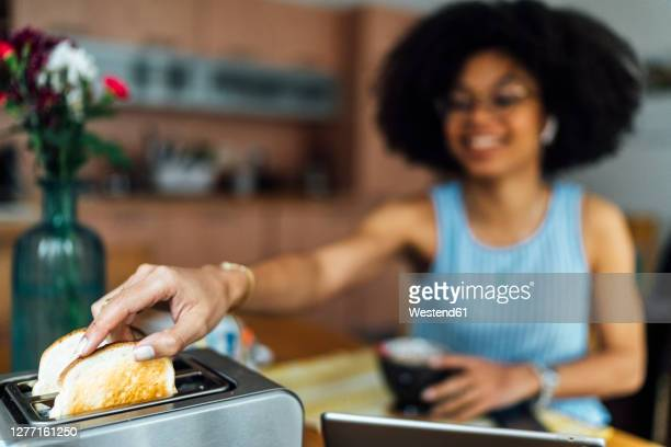 close-up of young woman toasting bread at home - making stock pictures, royalty-free photos & images