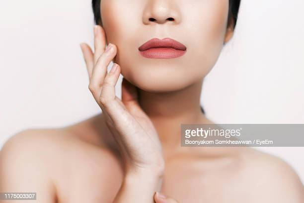 close-up of young woman touching cheek against white background - 頬 ストックフォトと画像