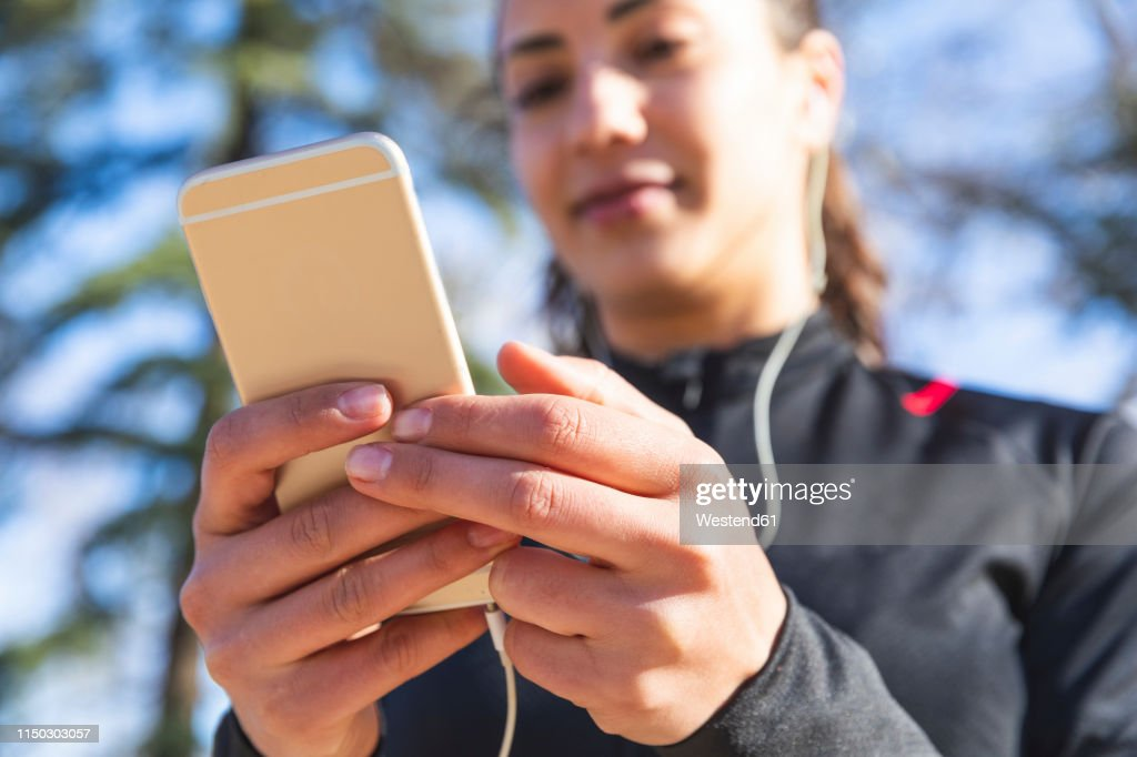 Close-up of young woman training and checking her smartphone : Foto de stock