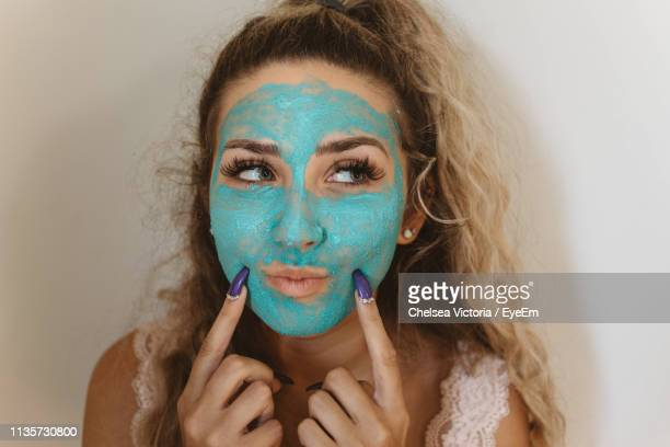 close-up of young woman wearing blue face mask at home - chelsea mask stock pictures, royalty-free photos & images