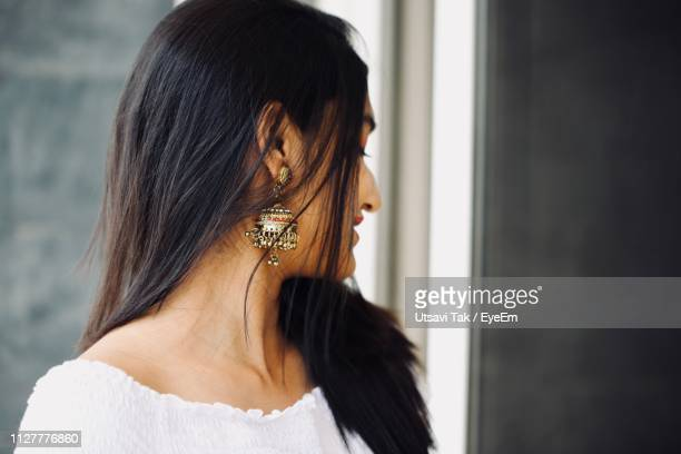close-up of young woman wearing earring - earring stock pictures, royalty-free photos & images