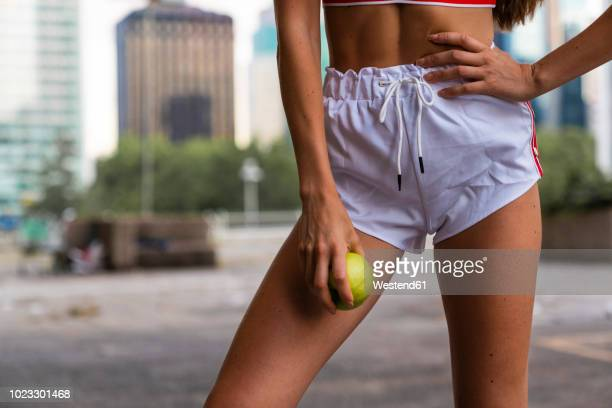 close-up of young woman wearing gym shorts holding an apple - ランニングショートパンツ ストックフォトと画像