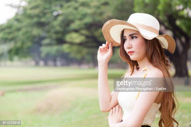 Close-Up Of Young Woman Wearing Hat While Sitting On Grass Field Against Sky