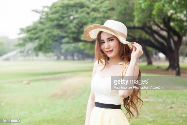 Close-Up Of Young Woman Wearing Hat While Standing On Grass Field Against Sky