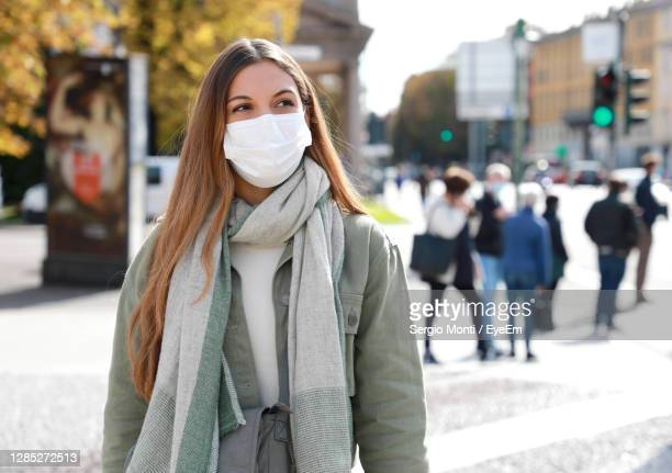 close-up of young woman wearing mask in city during winter - persona in secondo piano foto e immagini stock