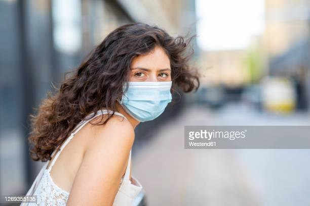 close-up of young woman wearing mask in city - sleeveless stock pictures, royalty-free photos & images