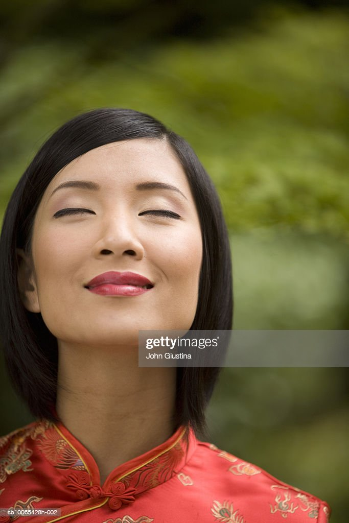 Close-up of young woman wearing red silk dress, eyes closed : Foto stock