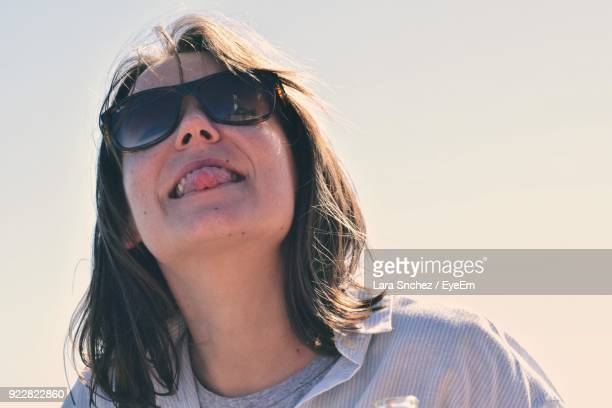 Close-Up Of Young Woman Wearing Sunglasses Against Clear Sky