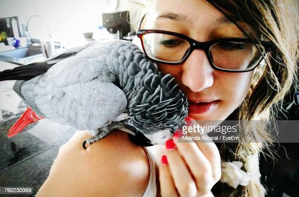 close-up of young woman with african grey parrot at home - perroquet photos et images de collection