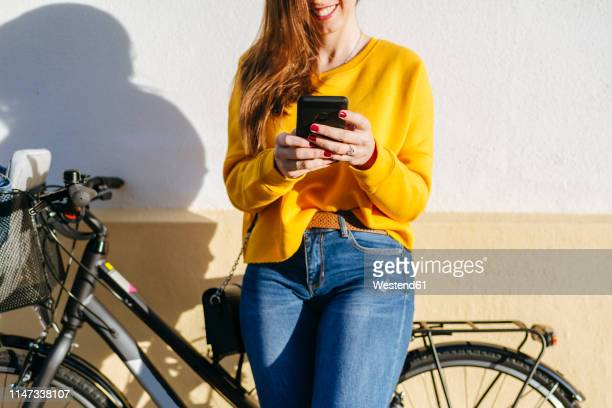 close-up of young woman with bicycle using cell phone at a wall - hands in her pants stock pictures, royalty-free photos & images