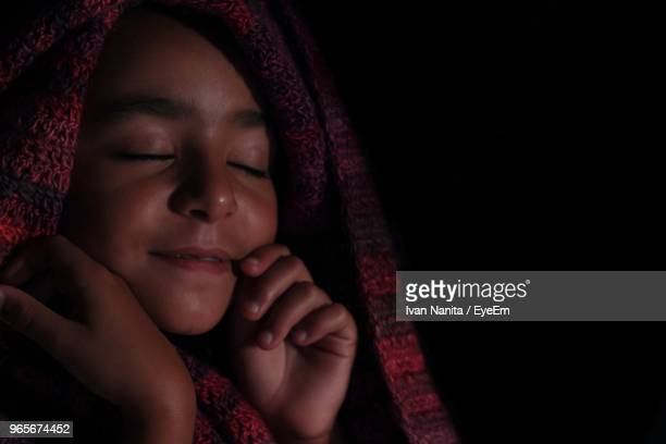Close-Up Of Young Woman With Blanket Against Black Background