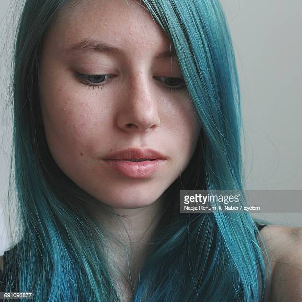 close-up of young woman with blue hair looking down - blue hair stock pictures, royalty-free photos & images