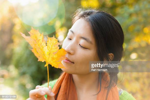 Close-up of young woman with closed eyes holding dry maple leaf at park on sunny day