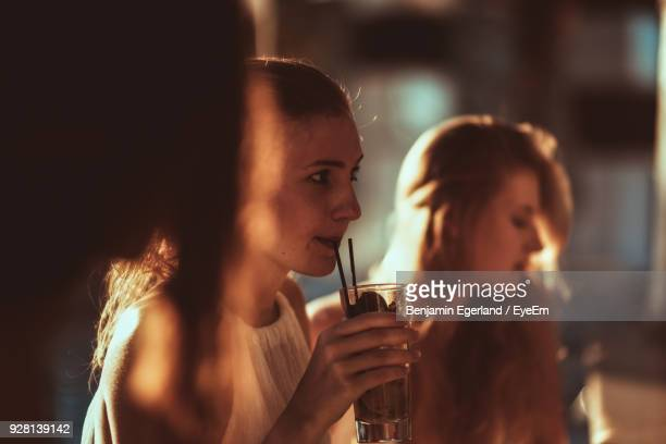 Close-Up Of Young Woman With Drink At Restaurant