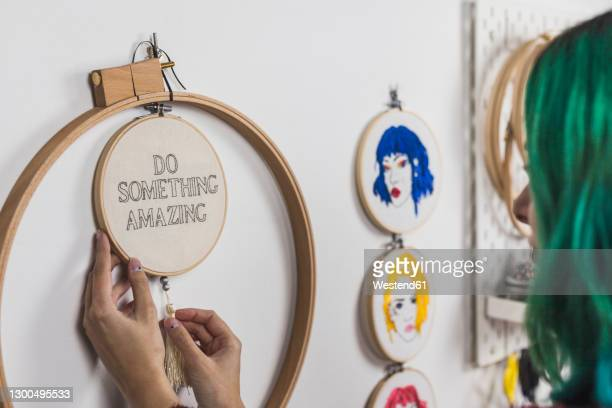 close-up of young woman with dyed hair hanging embroidery frame on wall - needlecraft stock pictures, royalty-free photos & images