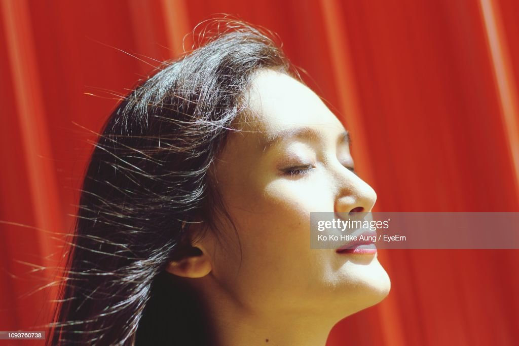 Close-Up Of Young Woman With Eyes Closed Against Red Wall : Stock Photo