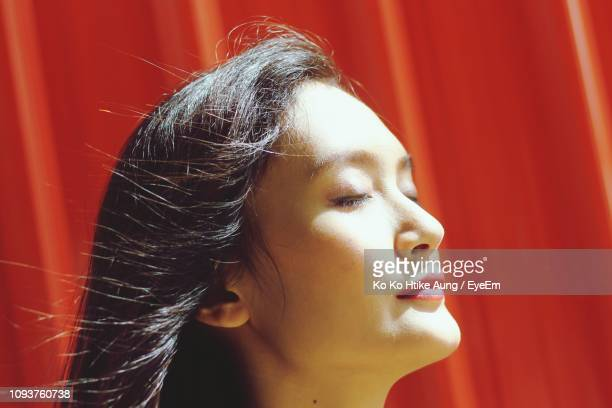 close-up of young woman with eyes closed against red wall - ko ko htike aung stock pictures, royalty-free photos & images