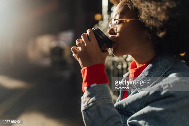 close-up of young woman with eyes closed drinking coffee while standing outdoors - drink stock pictures, royalty-free photos & images
