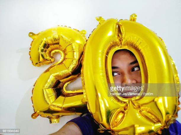 Close-Up Of Young Woman With Golden Number 20 Balloons By Wall