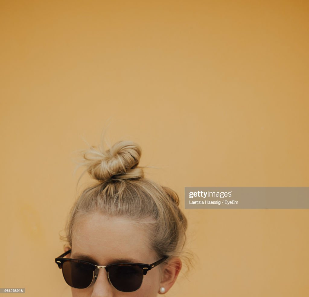 Close-Up Of Young Woman With Hair Bun Against Yellow Background : Stock Photo