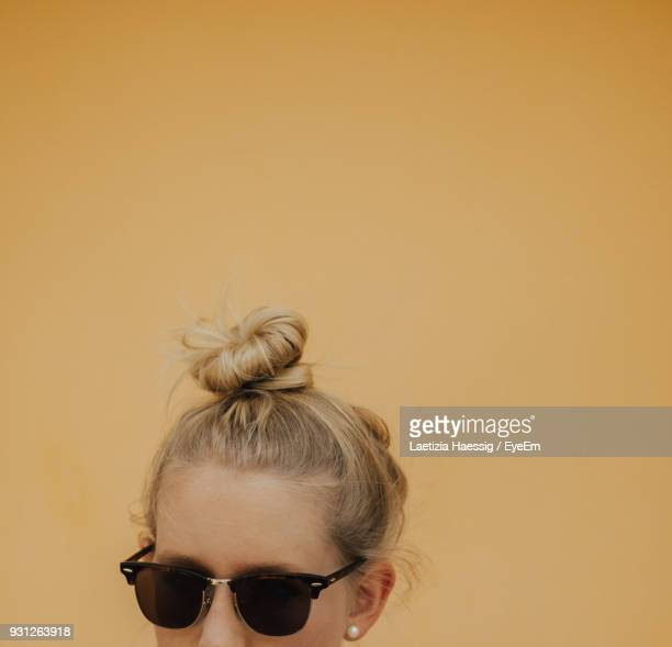 close-up of young woman with hair bun against yellow background - おだんごヘア ストックフォトと画像