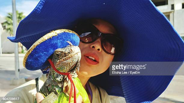 close-up of young woman with iguana wearing hat - iguana foto e immagini stock