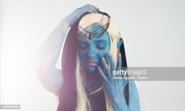 close-up of young woman with spooky make-up standing against white background - body paint stock pictures, royalty-free photos & images