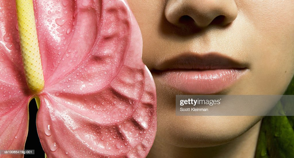 Close-up of young woman's face with Anthurium flower : Foto stock